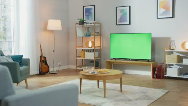 居心地の良いリビング ルーム、スタイリッシュな家具とデザイン、部屋の真ん中に緑のクロマ キー テレビ。カメラのショットでズームします。 - 居間点の映像素材/bロール
