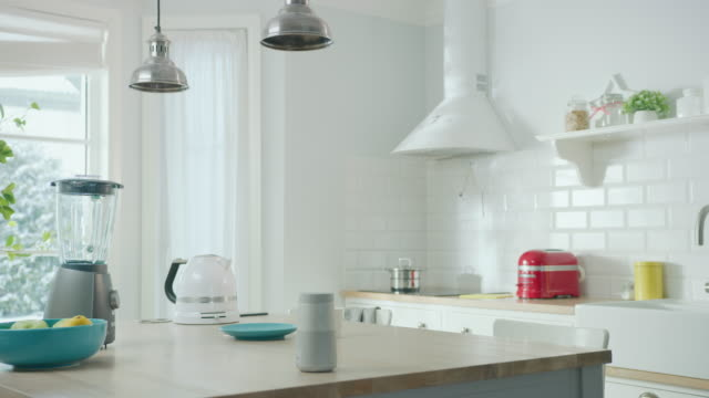 Cozy Modern Scandinavian Kitchen Interior with Electrical Appliances and Fruits. Empty Sunny Room with Wireless Speaker, Coffee Machine, Kettle and Toaster on a Wooden Table. Winter Snow Outside.