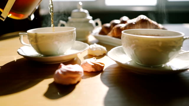 cozy morning moment. tea is poured into cups from french press. croissants and sweets. sweet breakfast breakfast. video footage - teapot stock videos & royalty-free footage