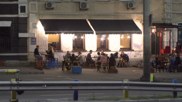 Cozy open-air cafe in the city at night with a car in the foreground, timelapse.