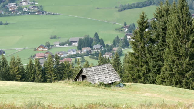 Cozy very old vintage wooden house in the Austrian Alps on a hill with green grass on the background of new modern houses, Old rural country wooden house in village video