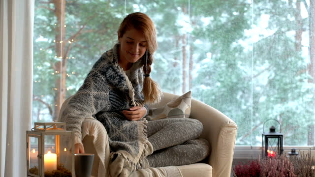 cozy winter lifestyle. young happy woman drinking cup of coffee wearing knitted sweater sitting home by the big window with winter snow background - calzino video stock e b–roll