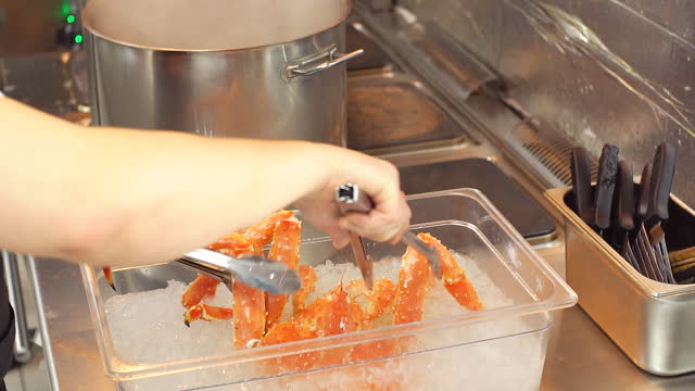 Crab being cooking pot by chef in kitchen