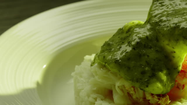 Crab Leg and Pesto over Rice Pouring Pesto and decorating with Crab Leg dish plated pesto sauce stock videos & royalty-free footage