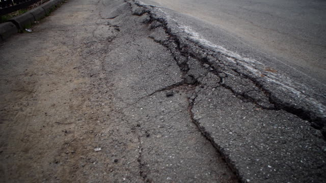 Crack of roadway surface on the old carriageway. Camera moves along deep cracks in asphalt. View of fault in road, consequences of natural disaster, earthquake or man-made disaster. earthquake stock videos & royalty-free footage