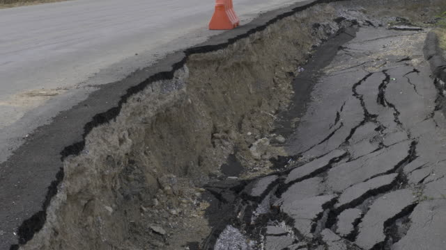 Cracked and broken asphalt road from earthquake