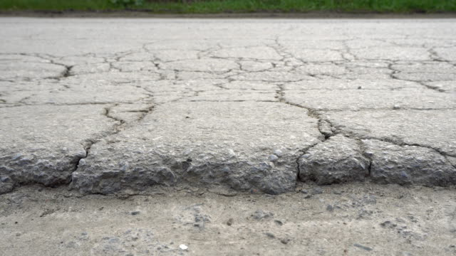 Cracked and broken asphalt road. Cracked and broken asphalt road. Bad road conditions. Dolly shot. depression land feature stock videos & royalty-free footage