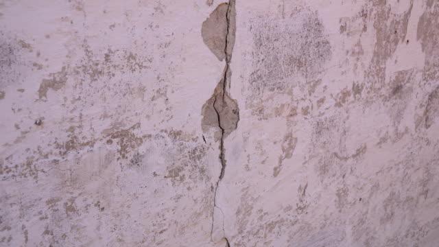 ひびの入った壁、ひびの入ったコンクリート、建物の解体。コンクリート壁の亀裂を増加します。 - セメント点の映像素材/bロール