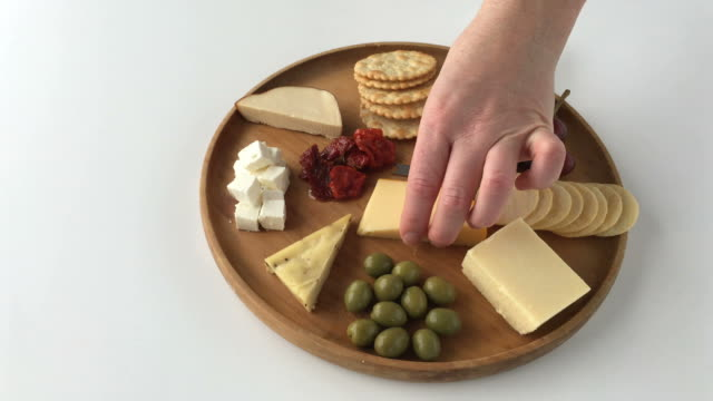 Crackers with cheese platter Woman hands serving crackers with cheese platter cheese stock videos & royalty-free footage