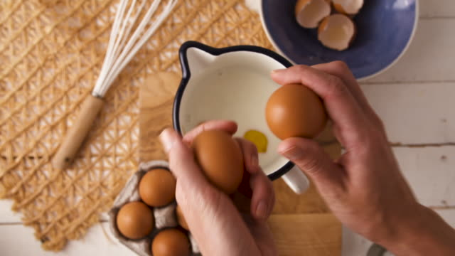 Cracking eggs Overhead view of eggs being cracked mixing bowl stock videos & royalty-free footage