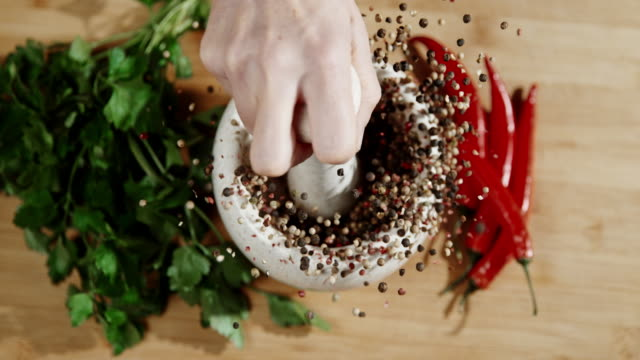 SLO MO Cracking peppercorns in the mortar Super slow motion shot of an unrecognizable person cracking peppercorns in the mortar. mortar and pestle stock videos & royalty-free footage