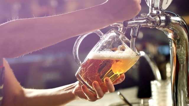 Craft beer poured into a glass Craft beer poured into a glass. lager stock videos & royalty-free footage