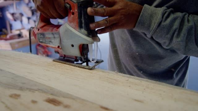 職人はサーフボードを形作るためにジグソーパズルを使用しています - 材木点の映像素材/bロール