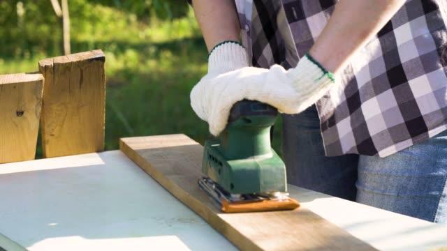 vídeos y material grabado en eventos de stock de artesanía mujer puliendo tablón de madera con lijadora eléctrica - tablón