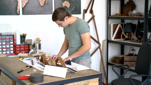 Craftsman assembling wooden project in his studio video