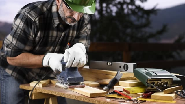 Craftsman at work on wooden boards. Carpentry. Adult carpenter craftsman wearing helmet and leather protective gloves, with the electric sander smoothes a wooden table. Construction industry, housework do it yourself. Safety at work. power tool stock videos & royalty-free footage