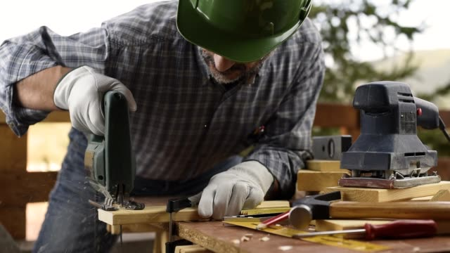 Craftsman at work on wooden boards. Carpentry. Adult carpenter craftsman wearing helmet and leather protective gloves, with electric saw working on cutting a wooden table. Construction industry, housework do it yourself. Footage. power tool stock videos & royalty-free footage
