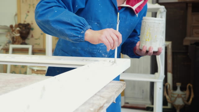 Craftsman carpenter painting a frame with brush video