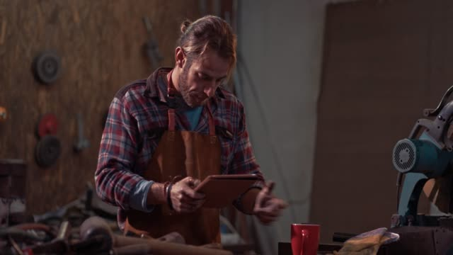 Craftsman doing research using tablet in industrial workshop