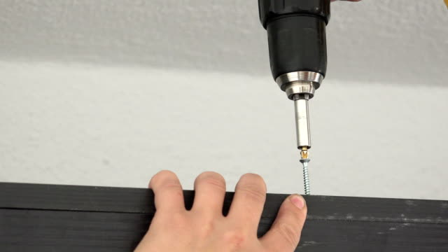 Craftsman drives the screw into furniture cabinet board with an electric powered screwdriver. Ungraded: DIY furniture assembly. Macro close-up video