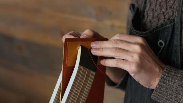 craftsman hand sewing a leather wallet - sztuka i rzemiosło wytworzony przedmiot filmów i materiałów b-roll