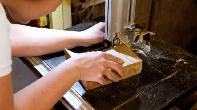 handwerker ist ein holz spielzeug autos werkstück aus holz mit bandsäge schneiden. - bandsäge stock-videos und b-roll-filmmaterial