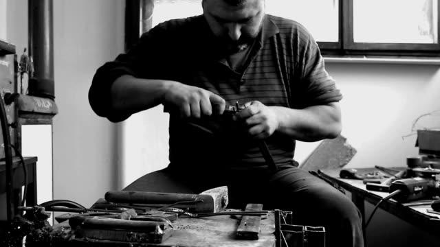 artigiano sta facendo figura con filo metallico nel suo laboratorio - fabbro ferraio video stock e b–roll
