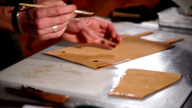 Craftsman is smearing adhesive on edge of cut detail for leather bag. video