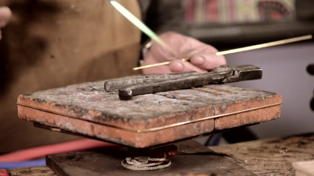 Craftsman jeweler creates a bracelet in his workshop video