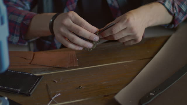 craftsman making leather key chain in home workshop. leather workshop - key ring stock videos & royalty-free footage