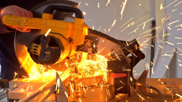 Craftsman sawing metal with disk grinder in sparks while grinding iron Craftsman sawing metal with disk grinder in sparks while grinding iron grinder industrial equipment stock videos & royalty-free footage