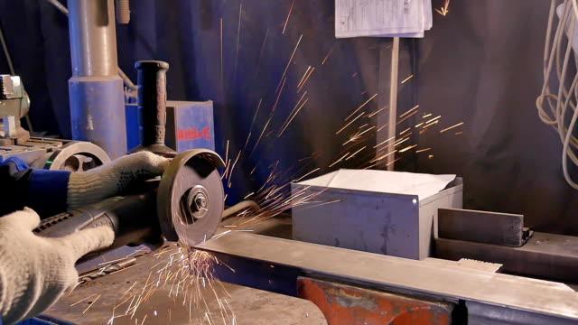 Craftsman sawing metal with disk grinder in workshop. Metal sawing close up. Worker in production sawing metal. Industry in slow motion Craftsman saw aluminium with disk grinder in workshop. Metal sawing close up. Industry in slow motion HD handbook stock videos & royalty-free footage