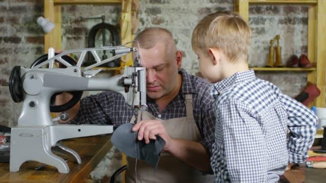 handwerker lehren kleinen sohn, wie man leder näht - schuhwerk videos stock-videos und b-roll-filmmaterial
