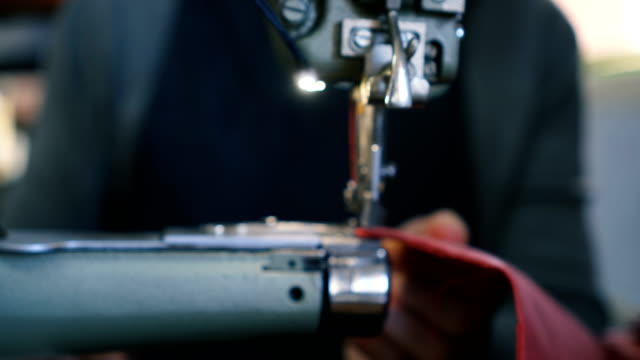 Craftsman works in workshop Mid-adult craftsman sewing leather on sewing machine in workshop. entrepreneur stock videos & royalty-free footage