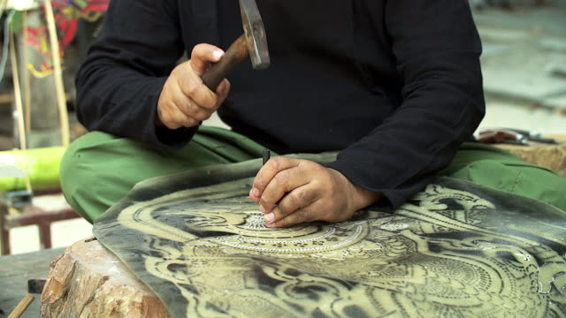 Craftsperson processing thai famous shadow puppet from buffalo leather, handicraft art in the southern region of Thailand (selective focus)