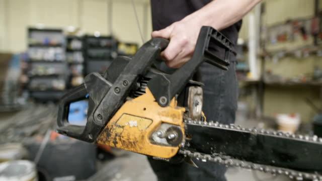 craftsperson starting powered chainsaw in workshop - motosega video stock e b–roll