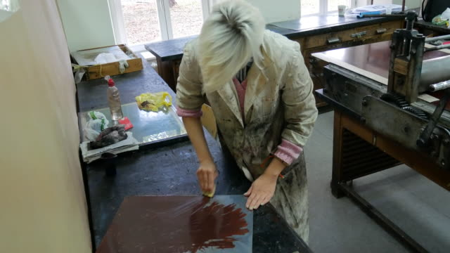craftswoman working applying dark ink on mould surface for intaglio print - литография стоковые видео и кадры b-roll