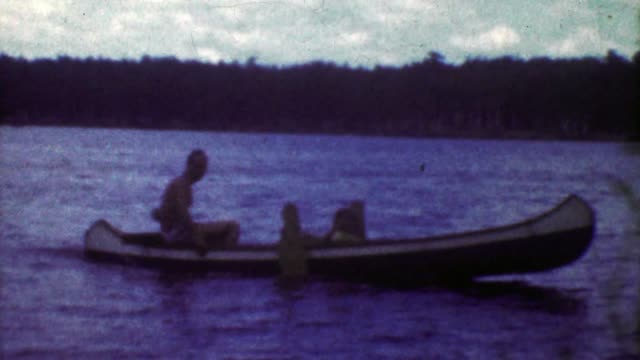 1953: Crafty man driving outboard motor rigged canoe across lake. video
