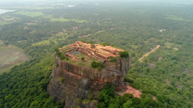 vídeos de stock e filmes b-roll de ws craggy,rock formation towering over lush green landscape,sri lanka, sigiriya - reserva natural