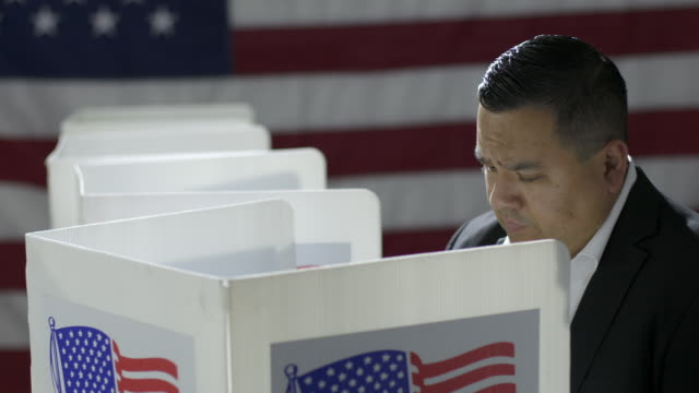 MCU Crane across to mixed race woman voting in booth at polling station 4K video