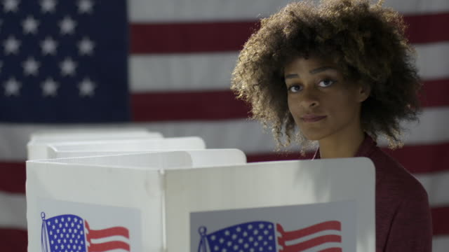 MCU Crane across to mixed race woman voting in booth at polling station video