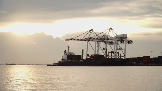 Crane and Container Ship in Industrial Port at sunset