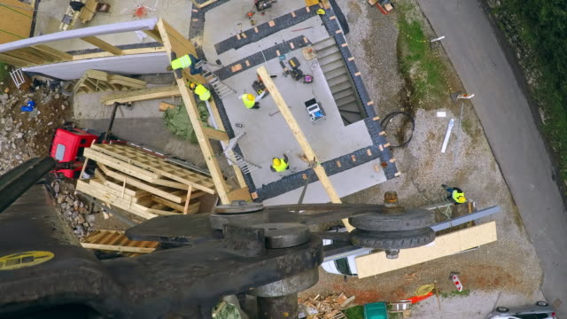 POV TIME-LAPSE Crane at the construction site of a house built from prefab wooden parts