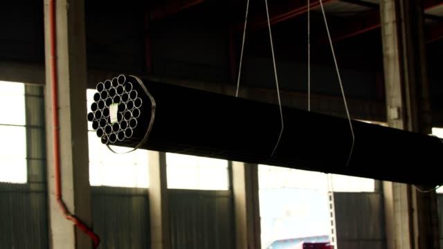 vídeos de stock, filmes e b-roll de gancho de guindaste com pilha de novos tubos de metal redondoe brilhantes - pesado peso