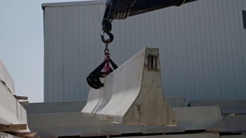gru che solleva una parte di una parete di cemento in un cantiere - calcestruzzo video stock e b–roll