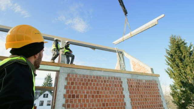 Crane lifting a wooden beam for the roof and the builders are observing the process