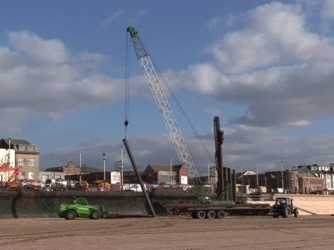Crane Lifting on Beach A Crane lifting up a metal bar on the beach - Tripod crane construction machinery stock videos & royalty-free footage