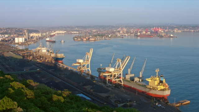 Crane on dock next to container ship in Durban harbour. Crane working on dock next to container ship in Durban harbour. Background shipping activity in habour. ports stock videos & royalty-free footage
