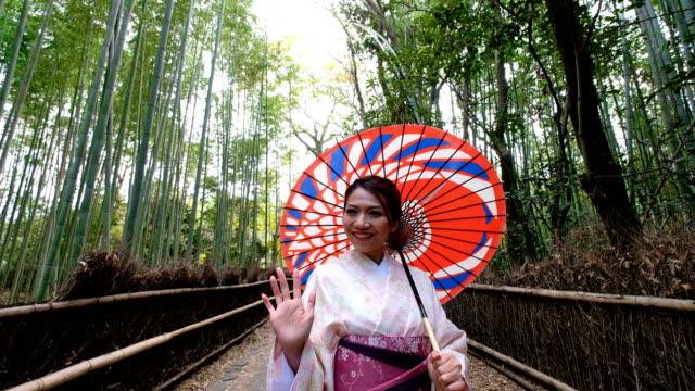 vidéos et rushes de 4k crane tir: une femme asiatique en costume traditionnel kimono avec pousse-pousse japonais à la forêt de bambous à arashiyama et sagano, kyoto, japon - vous accueille au japon - culture japonaise