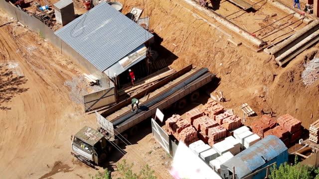 Crane unloads metal from truck. video